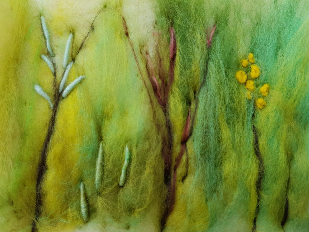 A needle felted picture. the background has a series of shades of green with vertical lines of brown fleece adding definition of grasses with yellow, pink and duck egg detail at the top of brown stems.