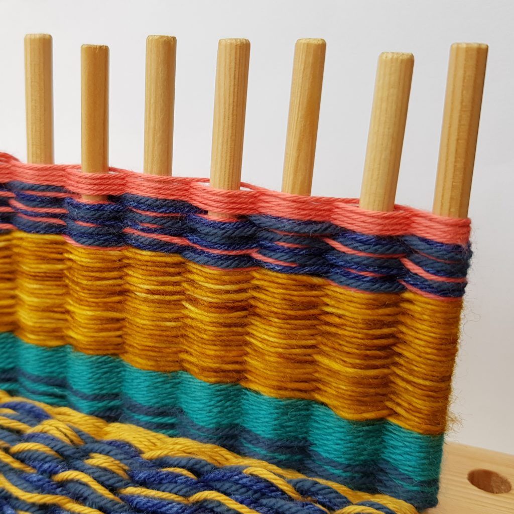 A peg loom with weaving on the pegs in strips. Colours include turquoise, mustard, navy and pink.