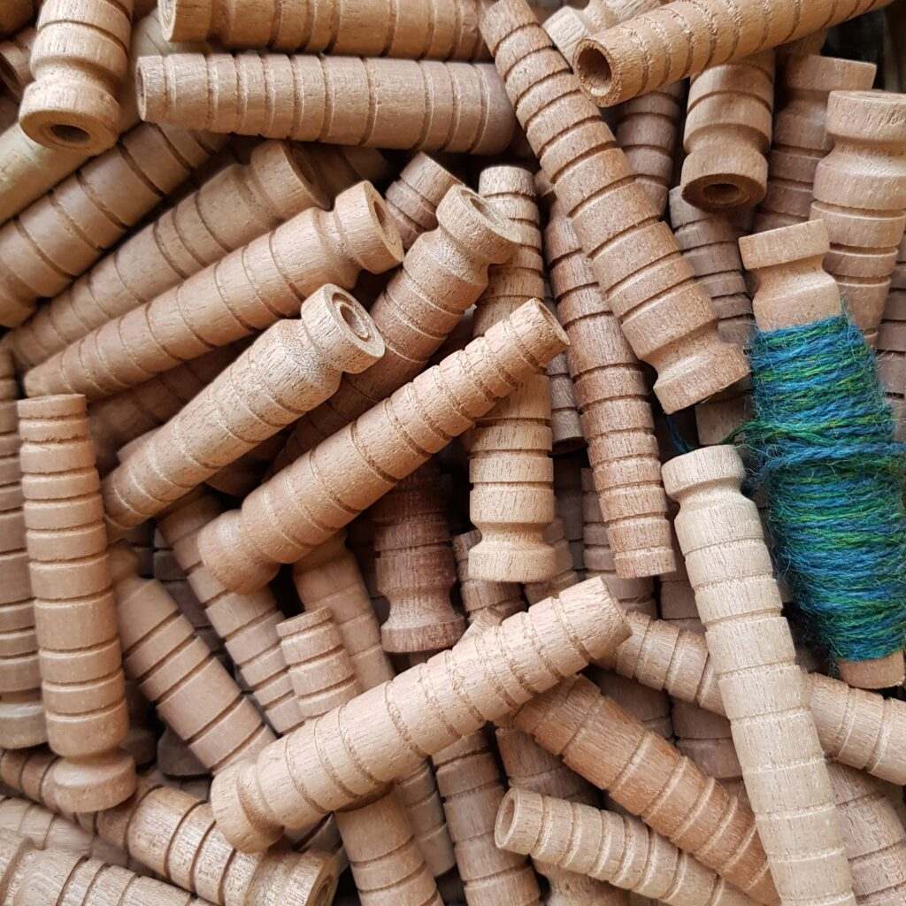 A pile of wooden weaving pirns. One has some green yarn wrapped around it.