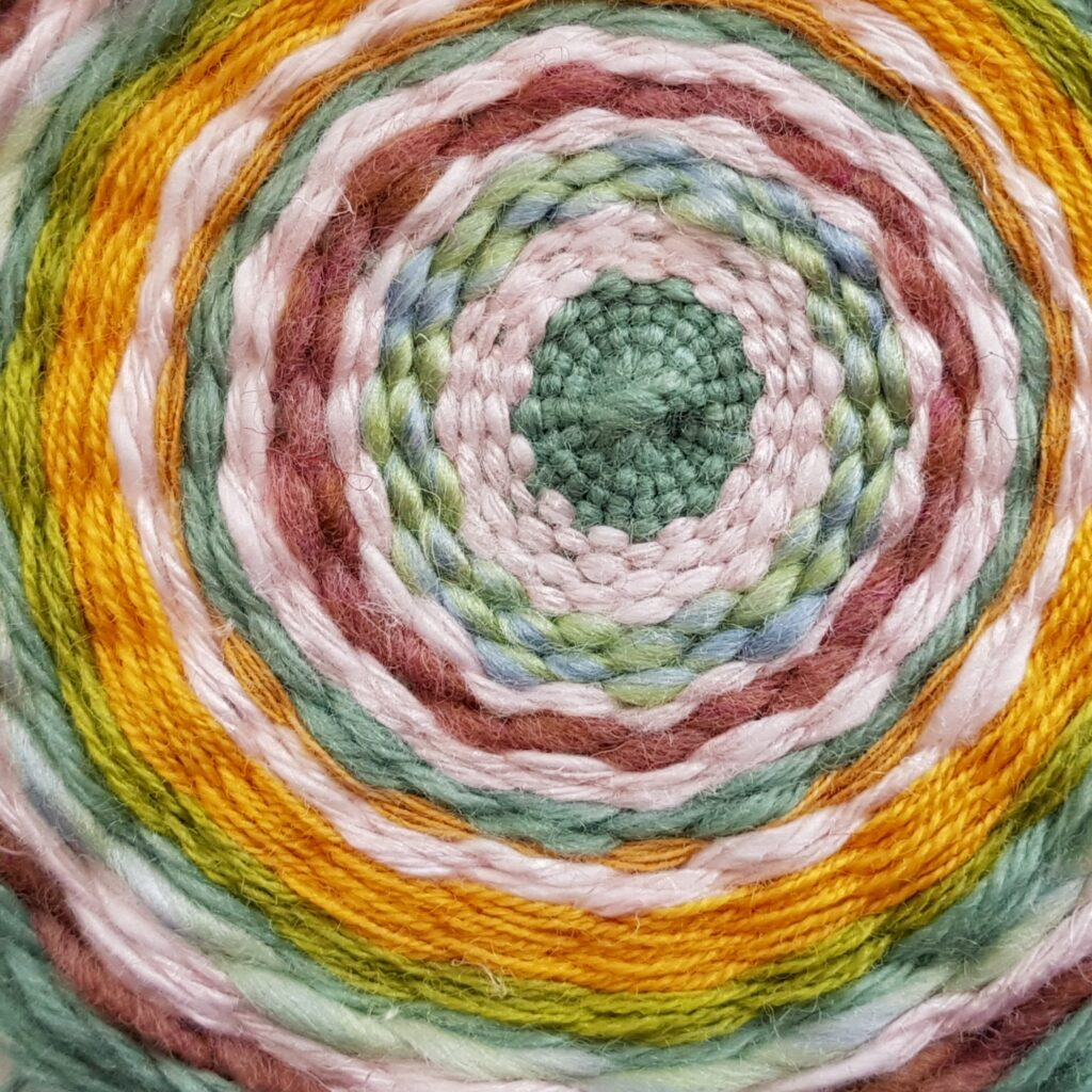 Detail of a piece of circular weaving using a range of yarns in spring colours including yellow, dark and light pink, pale and bright green.
