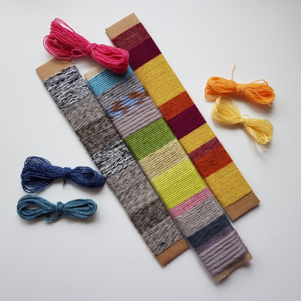 Three strips of cardboard wrapped in a series in a range of different coloured yarns. There are additional small bundles of yarn lying around as well.